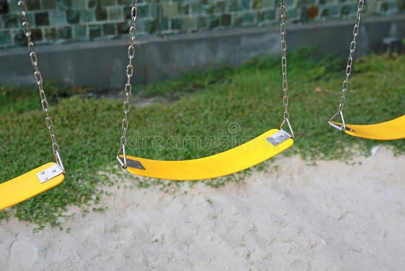黄色塑料摇摆在庭院里 免版税库存图片