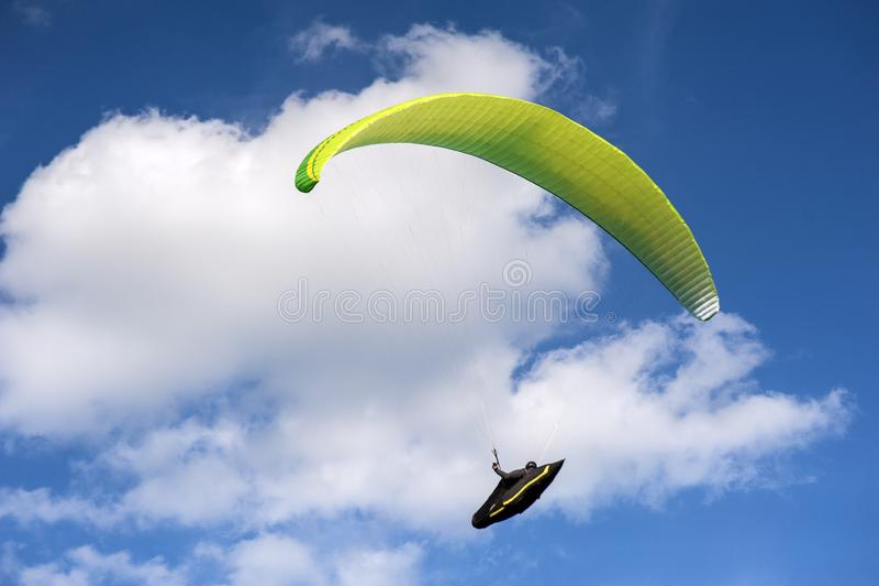 黄色和绿色滑翔伞是在天空蔚蓝的飞行以云彩为背景 库存照片
