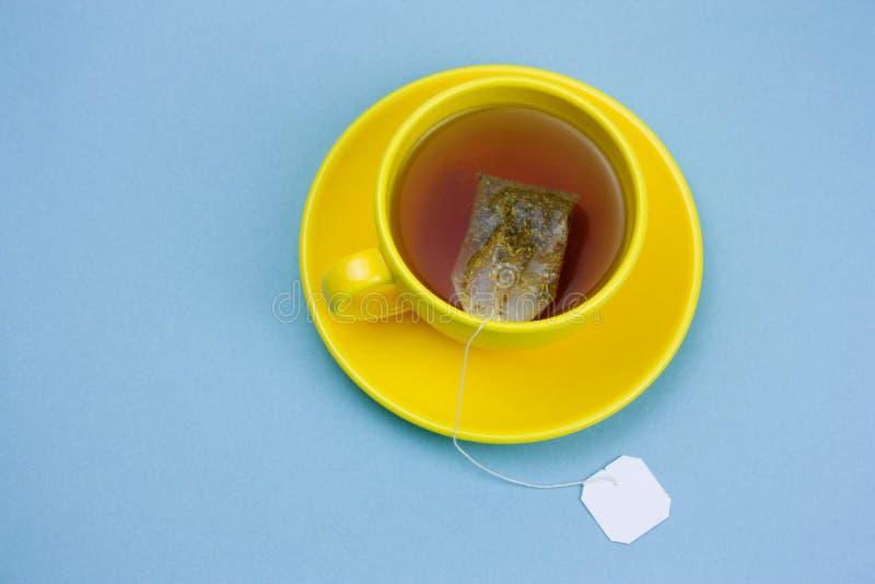 黄色杯子与茶包的热的茶与标签的白色嘲笑在蓝色背景 免版税库存图片
