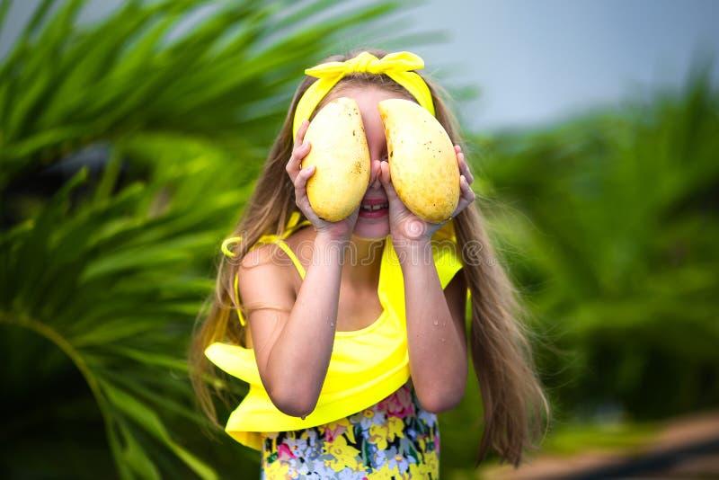 黄色泳装的可爱的女孩在度假拿着一个黄色芒果在热带 库存照片
