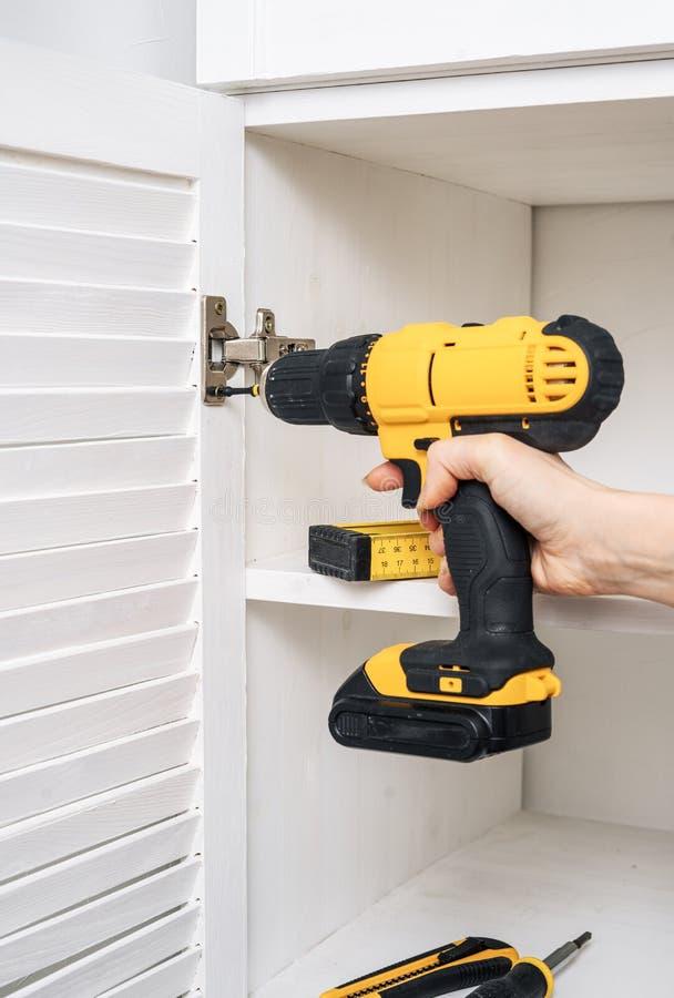 黄色螺丝刀在一只女性手上 家具铰链的设施在橱门的 图库摄影