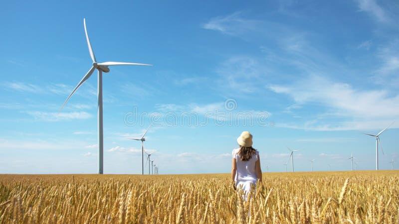 黄色麦田的美女与风车的电力生产的 库存图片
