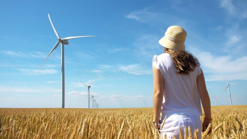 黄色麦田的美女与风车的电力生产的 免版税库存照片