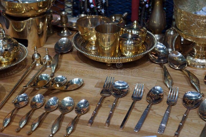 黄铜厨具、黄铜匙子、叉子和刀子在木桌背景 免版税库存图片