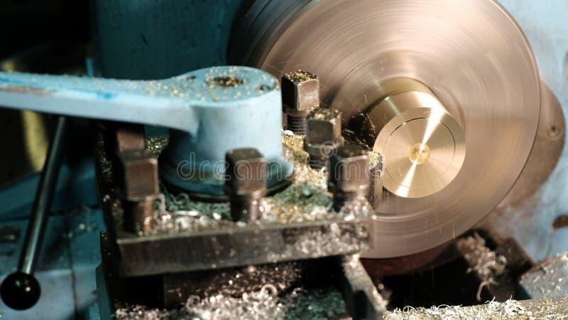 黄铜空白的饰面操作在翻转机的与切割工具 老转动的车床机器在转动的车间 库存图片