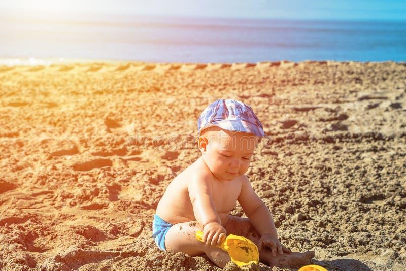 Één éénjarige babyjongen het spelen op het strand in de tijd van de de zomerdag stock foto's