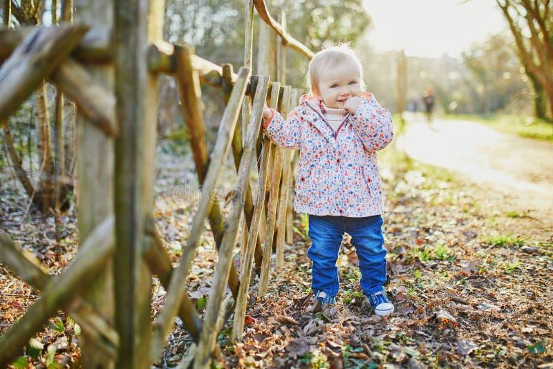 Één éénjarigemeisje die zich naast houten omheining in park bevinden stock foto