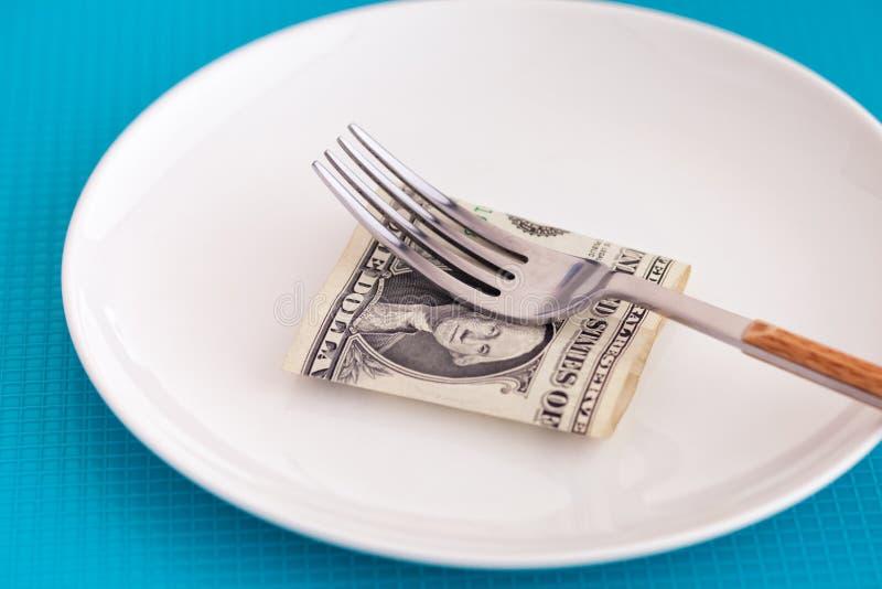 Één Amerikaanse dollar op een plaat met vork royalty-vrije stock afbeelding