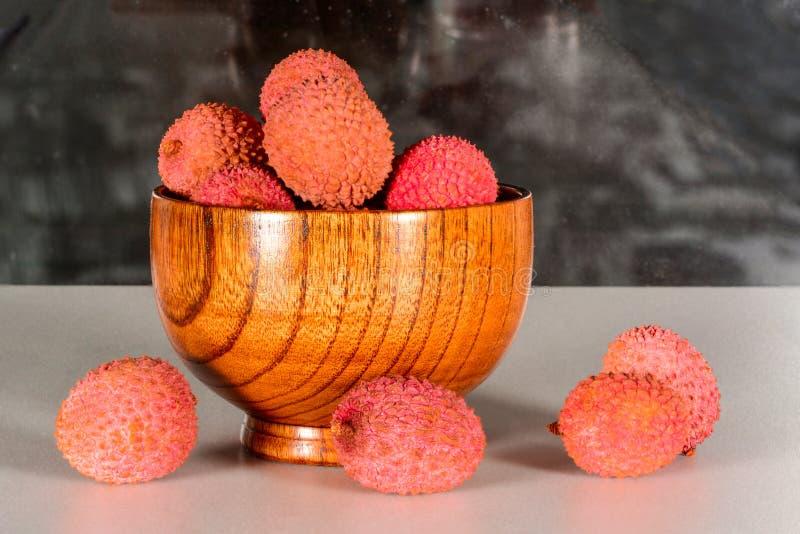 Één of ander vers lycheevruchten of litchi in bamboekom op een witte keukenlijst, sluiten omhoog stock afbeeldingen