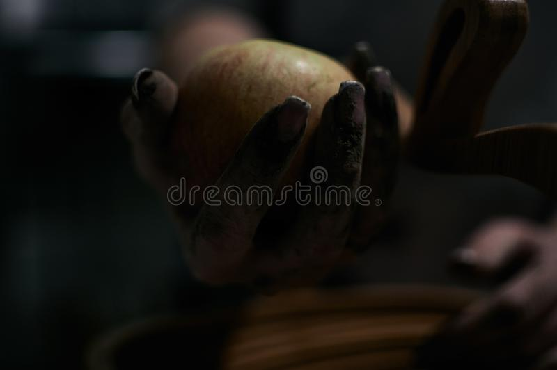 Één of andere applesjuicyappel in vuile handen stock afbeelding