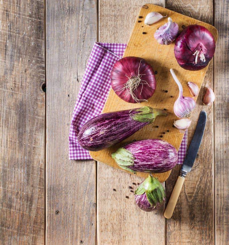 Één of andere aubergines, knoflook en rode ui op een houten raad Hoogste mening stock foto's