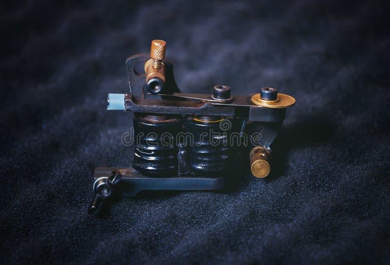 Één of andere tatoegeringsmachine - kader die met rollen op een zwarte, textuur liggen royalty-vrije stock afbeelding
