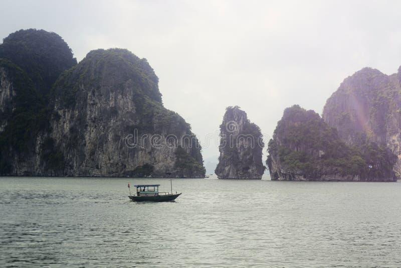 ??n boot op een overzees tussen rotsen in het water, Ha snakt de Baai van Baaihalong stock afbeeldingen