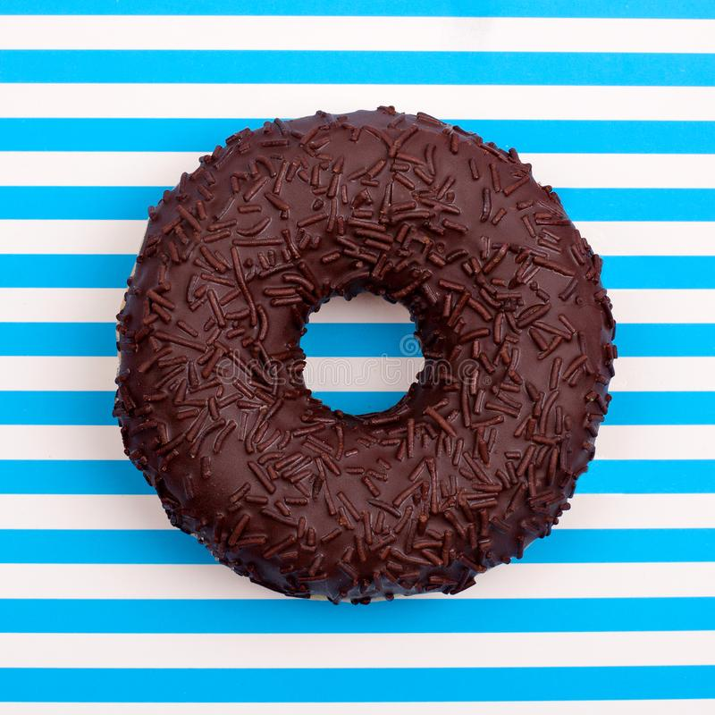 Één chocoladedoughnut op gestreepte blauwe en witte strepen achtergrond hoogste menings dichte omhooggaand stock fotografie