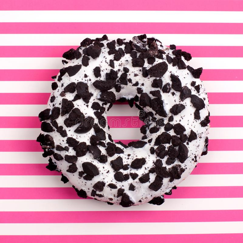 Één chocoladedoughnut op gestreepte roze en witte strepen achtergrond hoogste menings dichte omhooggaand stock foto