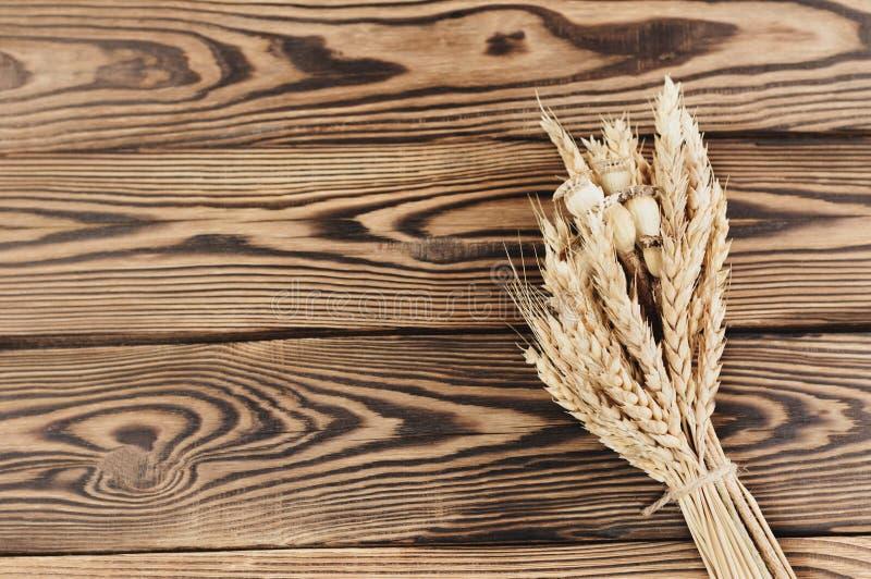 Één die bundel van tarwe en papaver van bruine kabel op oude houten planken wordt verbonden royalty-vrije stock afbeeldingen