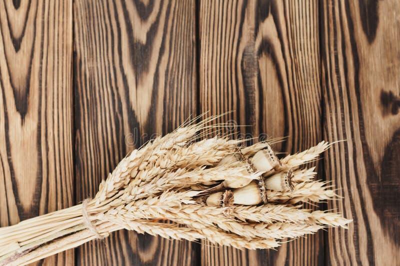 Één die bundel van tarwe en papaver van bruine kabel op oude houten planken wordt verbonden stock afbeeldingen