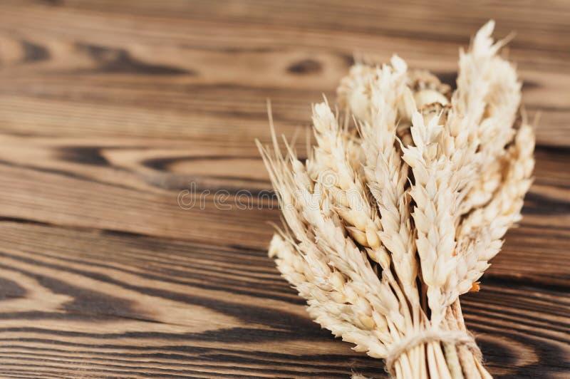 Één die bundel van tarwe en papaver van bruine kabel op oude houten planken wordt verbonden royalty-vrije stock foto