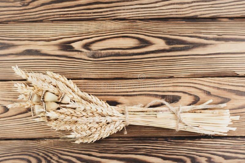 Één die bundel van tarwe en papaver van bruine kabel op oude houten planken wordt verbonden royalty-vrije stock fotografie