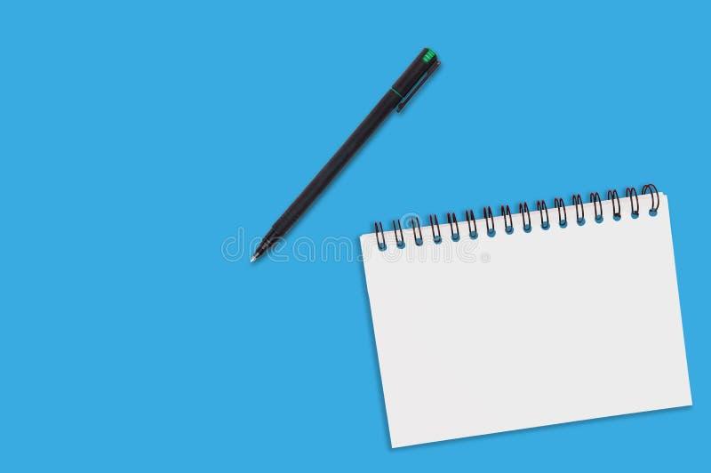 Één document blocnote met spiraalvormig bindmiddel en lege bladen dichtbij zwarte plastic pen ligt van blauwe bureaulijst Hoogste royalty-vrije stock foto's