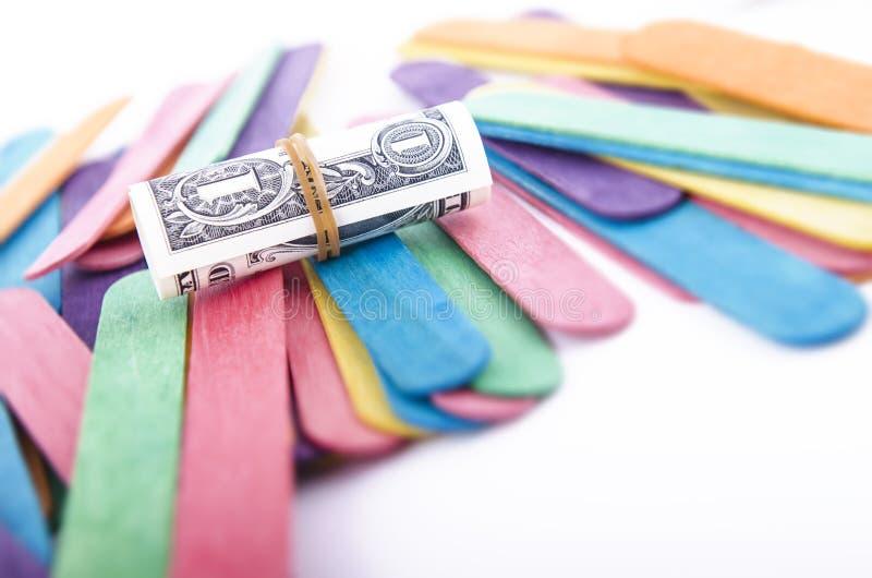 Één Dollar Bill Rolled in een Elastiekje stock foto