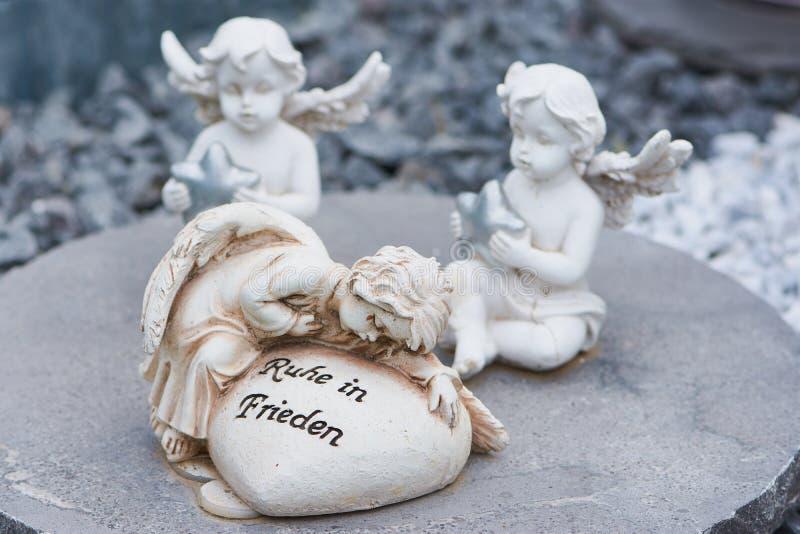 Één engel met een hart met de Duitse woorden voor rust in vrede royalty-vrije stock afbeeldingen