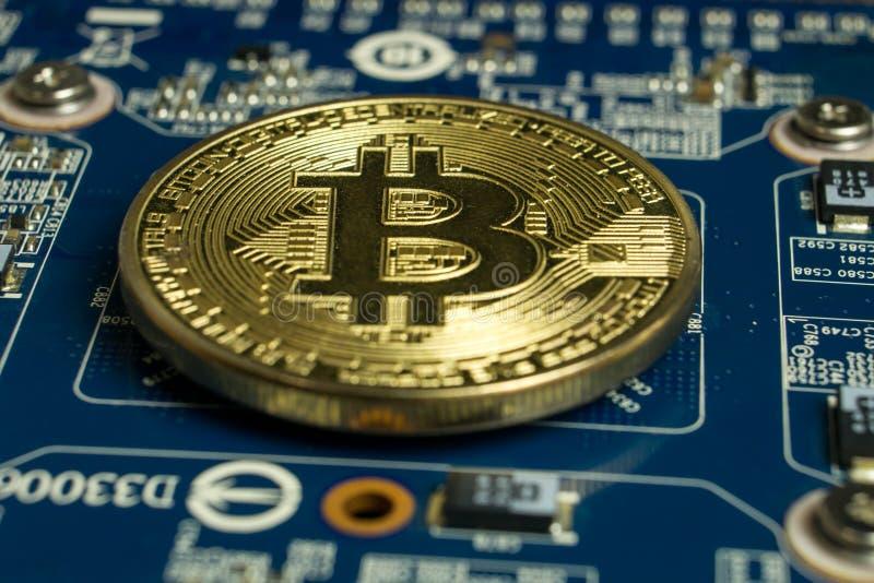 Één enkel Bitcoin-muntstuk op blauwe computermotherboard stock foto