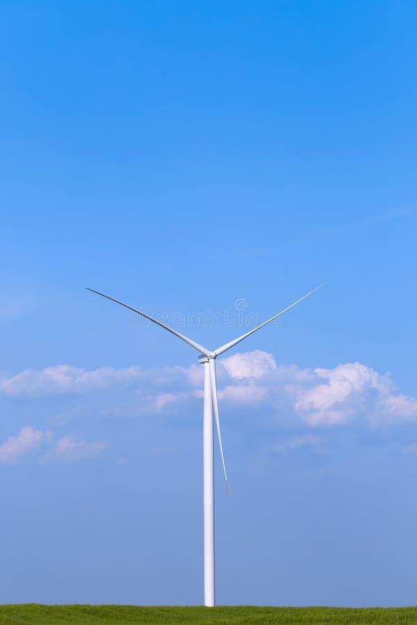 Één enkele windmolenturbine op groen landbouwgebied met blauwe hemel op achtergrond De Turbine van de duurzame energiewind stock foto
