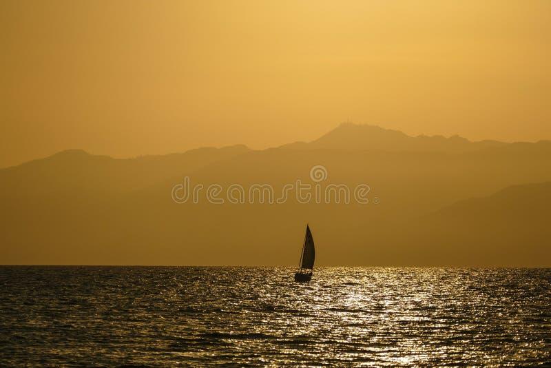 Één enkele zeilboot die in de oceaan bij zonsondergang varen royalty-vrije stock foto's