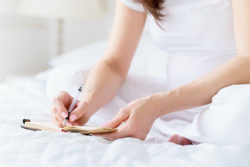 Één Europese zwangere vrouw schrijft sommige idee of thouths in notaboek door penzitting op wit bed van lichte ruimte bij zonnig royalty-vrije stock foto