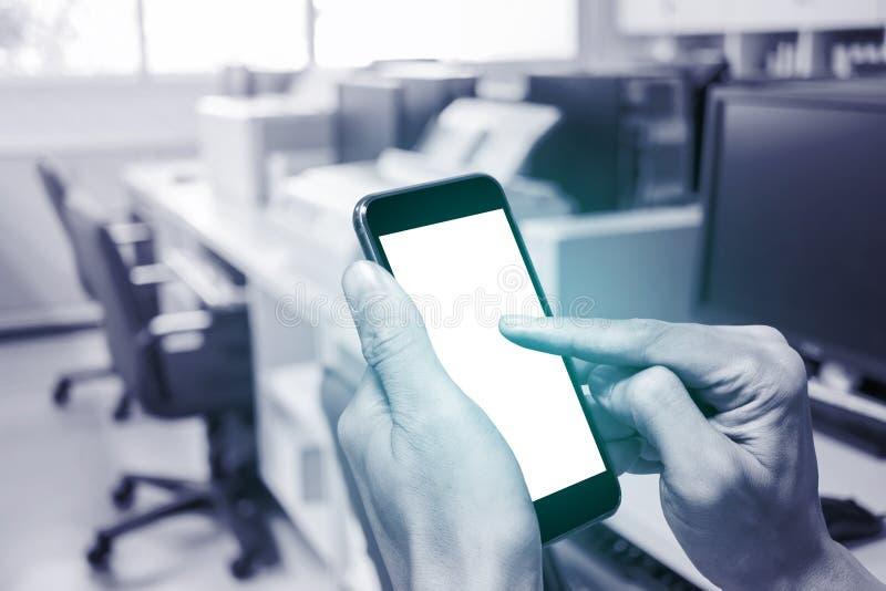 Één gebruikend smartphone in bureau stock fotografie