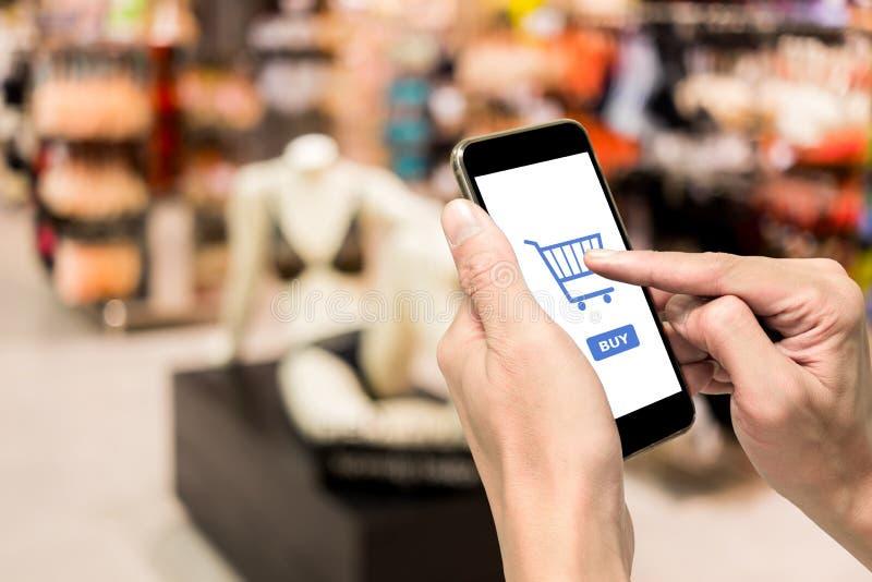 Één gebruikend smartphone om ondergoed te kopen stock foto