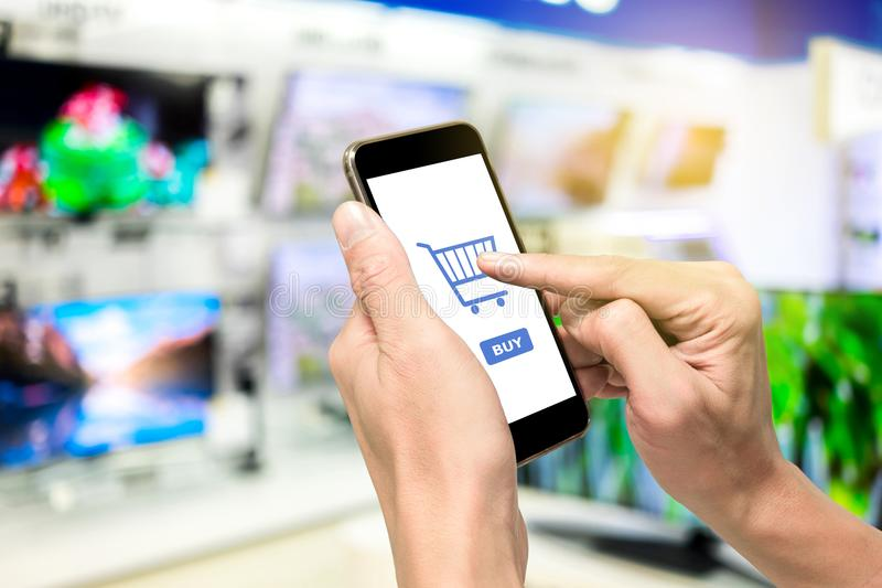 Één gebruikend smartphone om televisie te kopen royalty-vrije stock afbeeldingen