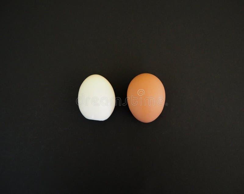 Één geheel ei en één ei zonder eierschaal op de zwarte stock fotografie