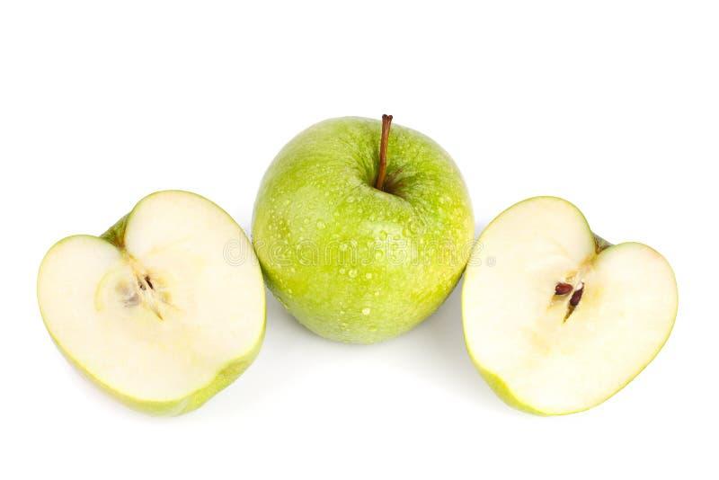 Één gehele grote groene appel en appelbesnoeiing in de twee helften in waterdalingen op witte achtergrond geïsoleerde dicht omhoo stock afbeeldingen