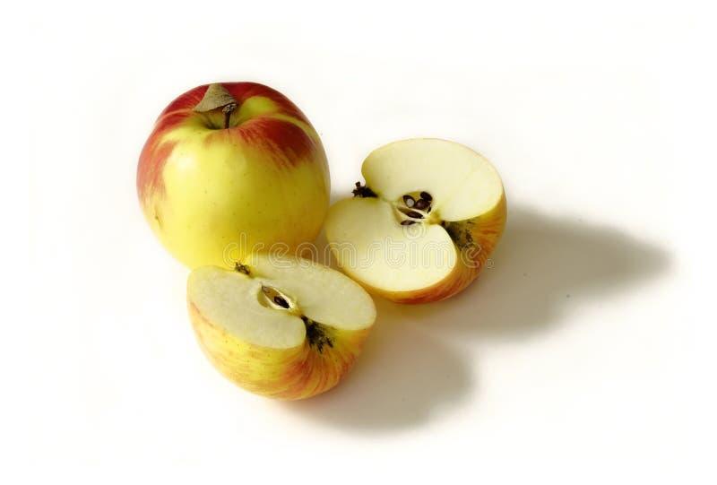 Één gele appel en de twee helften op een witte achtergrond horizonta stock foto