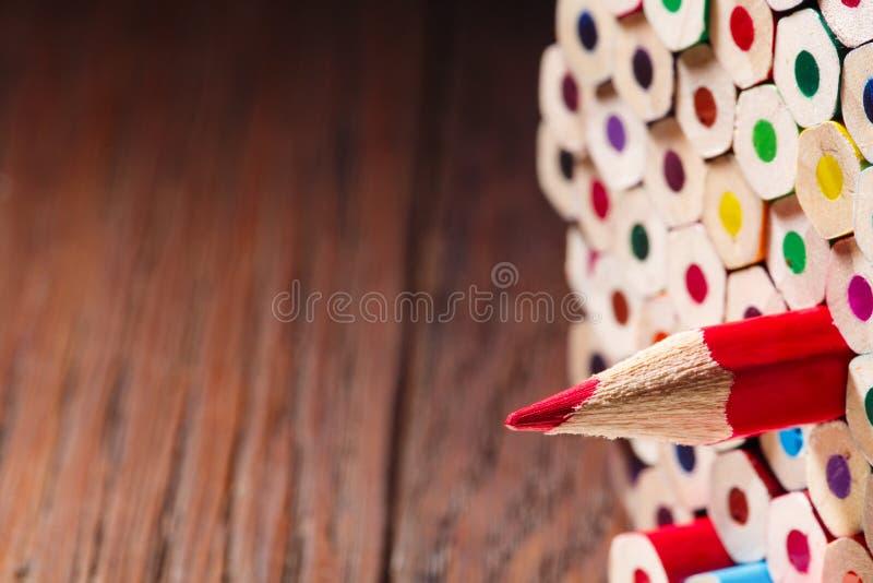 Één gescherpt rood potlood onder vele degenen stock foto's