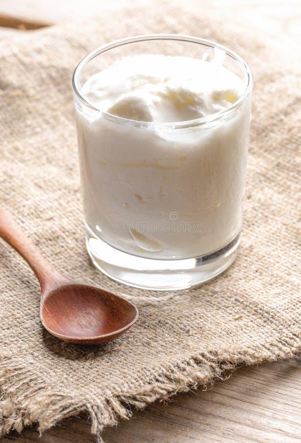 Één glas van yoghurt en houten lepel op juteservet op houten lijst royalty-vrije stock afbeeldingen