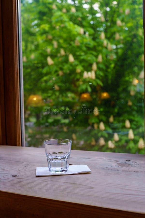 ??n glas water bevindt zich op een wit servet op een houten lijst dichtbij een venster overziend de weg met bloeiende kastanjebom stock fotografie