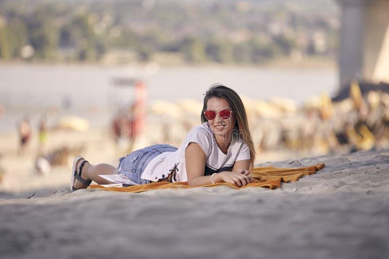 één glimlachend mooi jong meisje, die dragend gekleurde rode sunshades in openlucht stellen, royalty-vrije stock foto's