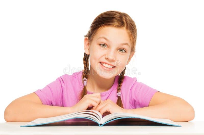 Één glimlachend schoolmeisje met haar handboek stock foto's
