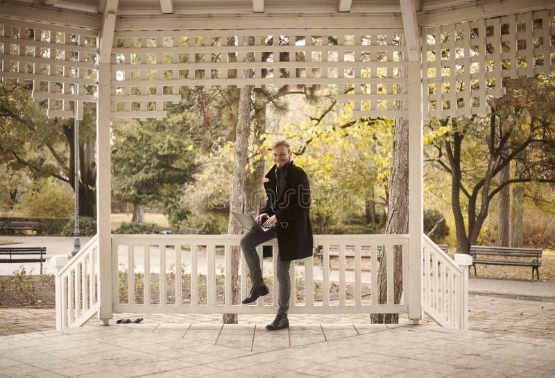 ??n glimlachende jonge mens, 20-29 jaar die oud, op omheining in openlucht in park zitten, terwijl het gebruiken van zijn laptop royalty-vrije stock fotografie