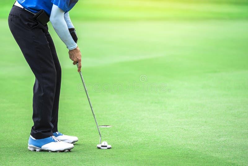 Één golfspeler zet een putter aan de bal om het gat te raken stock fotografie