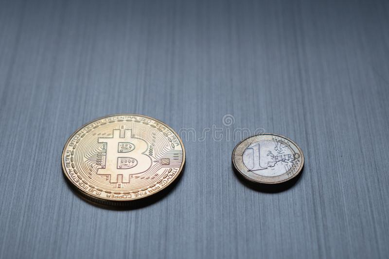 Één gouden bitcoin en één euro muntstuk op een metaalachtergrond C stock foto's