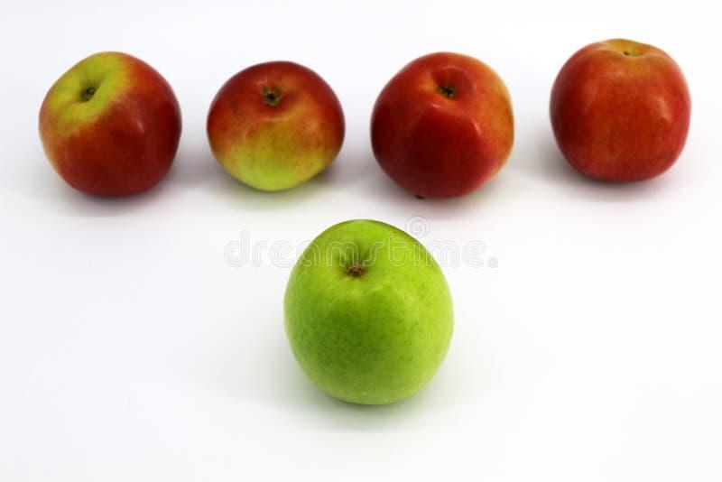 Één groen Apple tegenover vier rode appelen royalty-vrije stock afbeelding