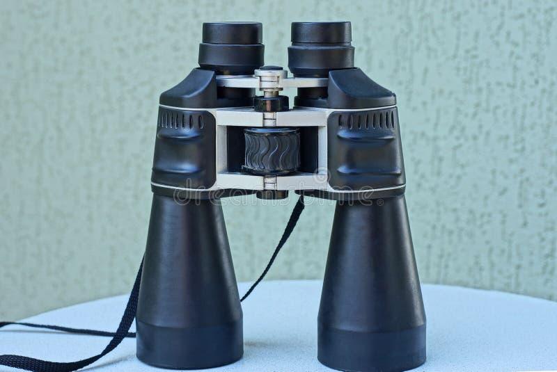 Één grote zwarte verrekijkerstribunes op een witte lijst royalty-vrije stock foto