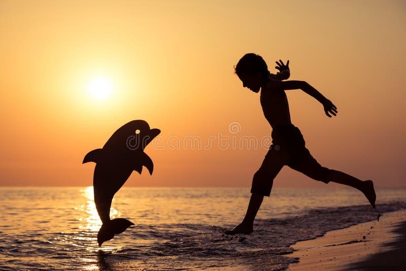 Één het gelukkige kleine jongen spelen op het strand in de zonsondergangtijd stock afbeeldingen