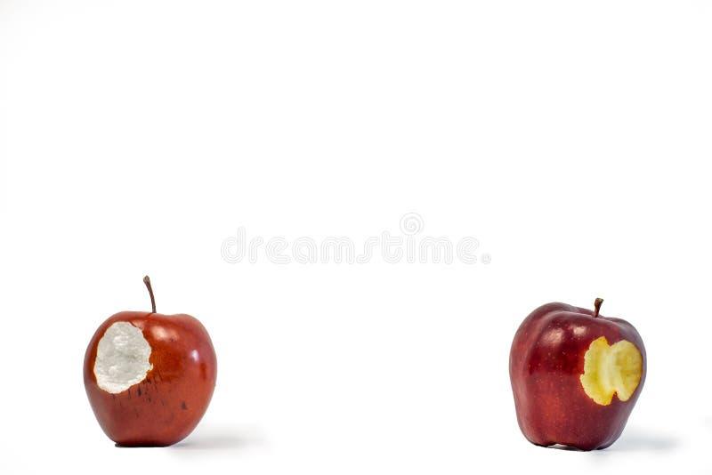 Één isoleerde valse rode appel en echte die appel met een beet uit het op een witte achtergrond wordt genomen royalty-vrije stock afbeelding