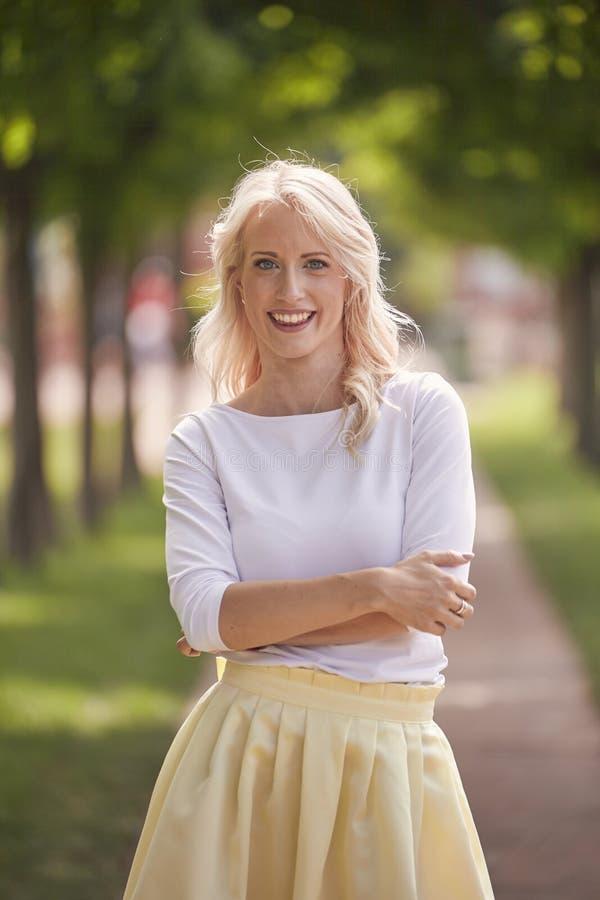 Één jong vrouwenportret, 25 jaar oude, gele kledings, witte bovenkant, park, gelukkig glimlachen stock foto