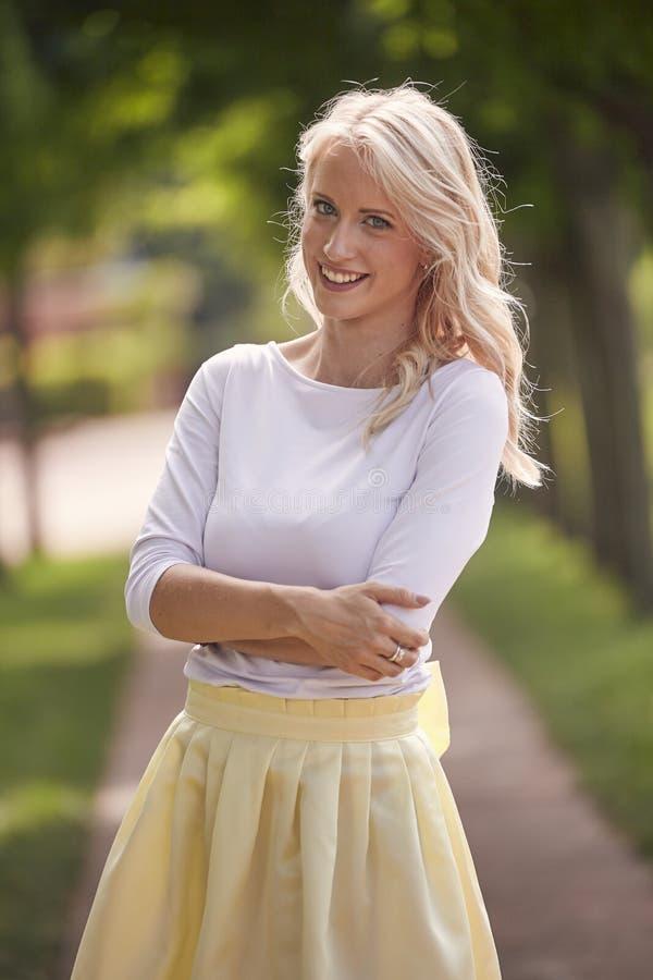 Één jong vrouwenportret, 25 jaar oude, gele kledings, witte bovenkant, park, gelukkig glimlachen royalty-vrije stock afbeelding